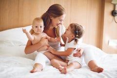 Счастливая мать семьи и 2 дет, сын и дочь в кровати Стоковая Фотография