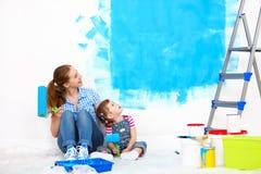 Счастливая мать семьи и дочь ребенка делая ремонты, красят wal стоковая фотография