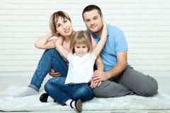 Счастливая мать семьи, отец и 2 дет играя и прижимаясь дома на поле Стоковое Изображение RF