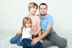 Счастливая мать семьи, отец и 2 дет играя и прижимаясь дома на поле Стоковые Изображения RF