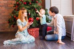 Счастливая мать семьи, отец и ребенок младенца маленький играя в зиме на праздники рождества Стоковые Фото