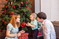 Счастливая мать семьи, отец и ребенок младенца маленький играя в зиме на праздники рождества Стоковые Изображения RF