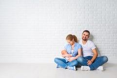 Счастливая мать семьи, отец newborn младенца на поле около blan Стоковое Изображение