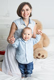 Счастливая мать с ее сыном в кровати Стоковая Фотография