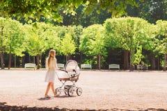 Счастливая мать с прогулочной коляской в парке стоковое фото rf