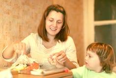 Счастливая мать с cookis девушки в кухне стоковые изображения