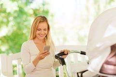 Счастливая мать с smartphone и прогулочной коляской в парке Стоковые Изображения
