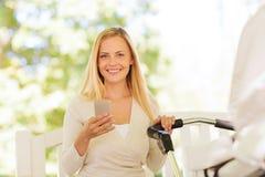 Счастливая мать с smartphone и прогулочной коляской в парке Стоковое Изображение