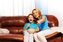 Счастливая мать указывая на смеяться над ТВ и сына Стоковая Фотография