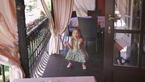 Счастливая маленькая белокурая девушка скачет в балкон акции видеоматериалы