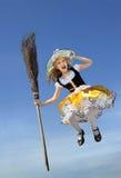 Счастливая маленькая ведьма при веник летая высоко над землей Стоковая Фотография