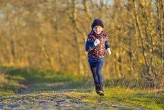 Счастливая маленькая девочка бежать в солнечном свете Стоковые Фотографии RF