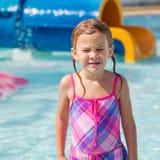 Счастливая маленькая девочка брызгая в бассейне стоковые изображения rf