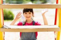 Счастливая маленькая девочка взбираясь на спортивной площадке детей Стоковое Фото