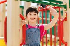 Счастливая маленькая девочка взбираясь на спортивной площадке детей Стоковые Изображения
