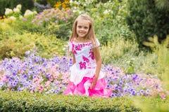 Счастливая маленькая девочка в длинном платье на цветнике Стоковые Фотографии RF