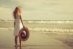Счастливая маленькая девочка в шляпе идя на пляж Стоковые Фото