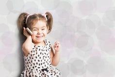 Счастливая маленькая девочка говоря на телефоне Голубой пузырь речи вверху фото для вашего текста Стоковое фото RF