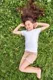 Счастливая маленькая девочка лежа на зеленой траве стоковая фотография rf