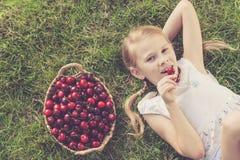 Счастливая маленькая девочка лежа около дерева с корзиной вишен Стоковая Фотография