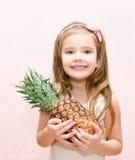Счастливая маленькая девочка держа зрелый весь ананас Стоковое Изображение RF