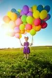 Счастливая маленькая девочка держа красочные воздушные шары Ребенок играя на a стоковое фото