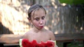 Счастливая маленькая девочка есть арбуз на пляже акции видеоматериалы