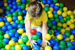 Счастливая маленькая девочка играя на красочной пластичной спортивной площадке шариков Стоковое фото RF