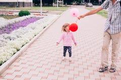 Счастливая маленькая девочка играя с красочной игрушкой раздувает outdoors Стоковая Фотография