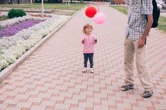 Счастливая маленькая девочка играя с красочной игрушкой раздувает outdoors Стоковые Изображения