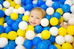 Счастливая маленькая девочка имея потеху в яме шарика в центре игры детей крытом Ребенок играя с красочными шариками в бассейне ш Стоковые Фото