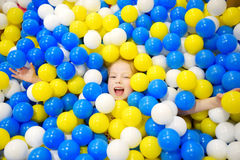 Счастливая маленькая девочка имея потеху в яме шарика в центре игры детей крытом Ребенок играя с красочными шариками в бассейне ш Стоковое фото RF
