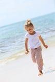 Счастливая маленькая девочка имея потеху на пляже Стоковые Изображения RF