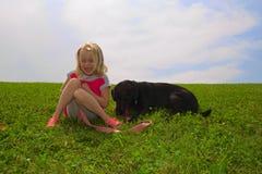 Счастливая маленькая девочка и черная лаборатория Стоковые Изображения RF