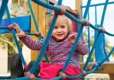 Счастливая маленькая девочка на ориентированной на действи спортивной площадке стоковое фото rf