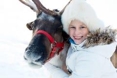 Счастливая маленькая девочка обнимая ее северный оленя Playtime зимы стоковое фото rf
