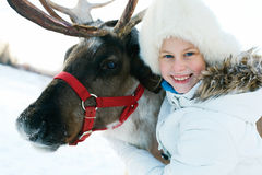 Счастливая маленькая девочка обнимая ее северный оленя Playtime зимы стоковые фото