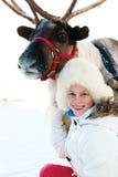 Счастливая маленькая девочка обнимая ее северный оленя Playtime зимы стоковое изображение rf