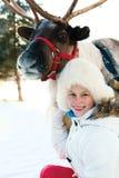 Счастливая маленькая девочка обнимая ее северный оленя Playtime зимы стоковое изображение