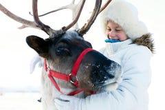 Счастливая маленькая девочка обнимая ее северный оленя Playtime зимы стоковое фото