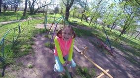 Счастливая маленькая девочка отбрасывает на see-saw видеоматериал