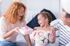 Счастливая маленькая девочка получая настоящий момент от ее дедов Стоковые Изображения RF