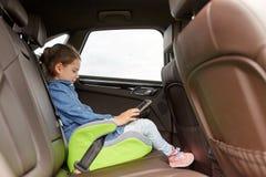 Счастливая маленькая девочка при ПК таблетки управляя в автомобиле стоковое фото