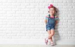 Счастливая маленькая девочка ребенка смеясь над на пустой кирпичной стене Стоковые Фото