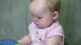 Счастливая маленькая девочка сидя и играя с шариком акции видеоматериалы