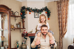 Счастливая маленькая девочка сидя на шеи ` s папы Стоковая Фотография
