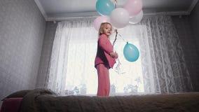 Счастливая маленькая девочка скача около окна на кровати в питомнике с пуком воздушных шаров в ее руках и сток-видео