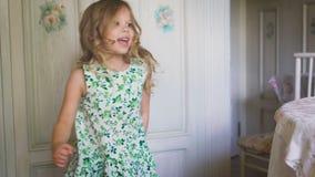 Счастливая маленькая девочка скачет в светлую комнату акции видеоматериалы