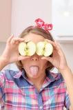 Счастливая маленькая девочка с 2 яблоками около ее глаз показывая ей toung Стоковое Фото