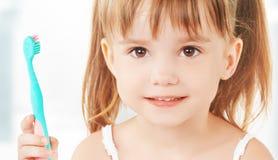 Счастливая маленькая девочка чистя ее зубы щеткой Стоковая Фотография